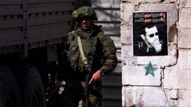 Bewaffneter Soldat steht neben einer Mauer, auf der ein Plakat mit dem Konterfei von Baschar al-Asssad hängt.