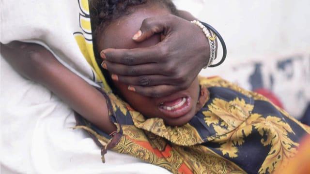 Jemand hält den Kopf eines somalischen Mädchens und hält ihr die Augen zu.