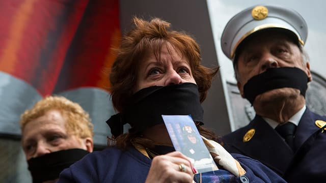Menschen protestieren mit verbundenem Mund.