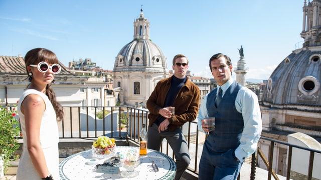 Eine Frau und zwei Männer stehen auf einer Terrasse.