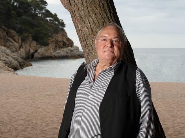 Porträt Mathias Gnädinger, im Hintergrund eine Meeresbucht.