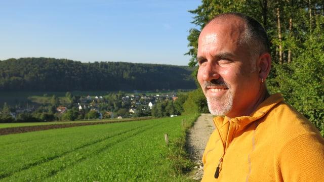 Gemeindepräsident Florian Kron an einem sonnigen Tag, im Hintergrund Hersberg.