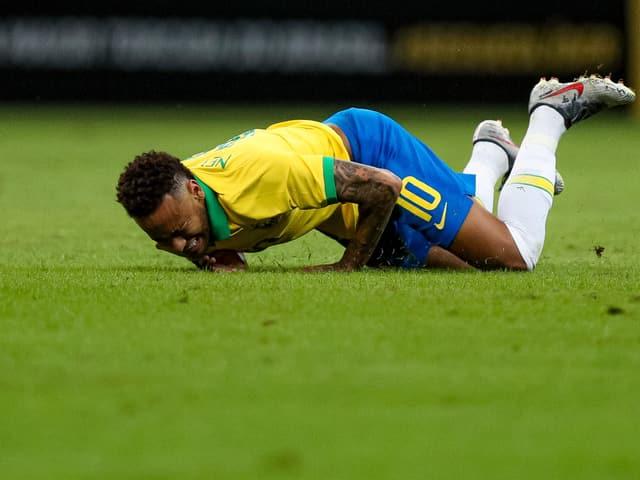 Neymar wälzt sich mit Schmerzen auf dem Rasen.
