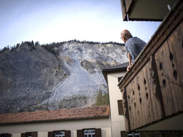 Ein Mann auf einem Balkon blickt Richtung Berg, wo bereits einiges an Geröll zu Tal gedonnert ist.