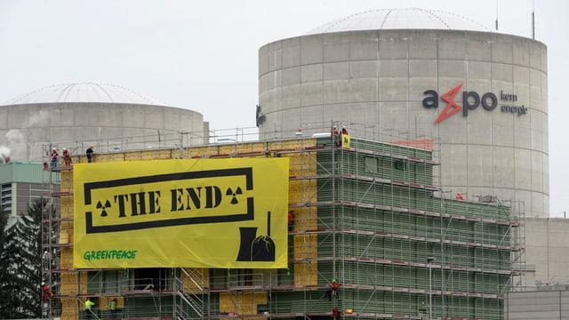 Aktivisten von Greenpeace montieren ein gelbes Plakat mit der Aufschrift «The End» am AKW.