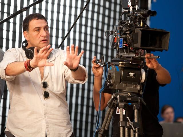 Regisseur in weissem Hemd steht neben der Kamera, Hände in der Luft.