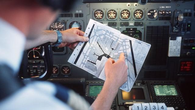 Pilot im Cockpit. Er hält einen Plan in der Hand, auf dem vermutlich eine Flughafen-Anlage aufgezeichnet ist. Im Hintergrund sind unzählige Messgeräte und Displays sichtbar.