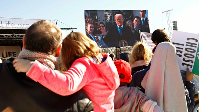 Donald Trump auf grossem Bildschirm vor Publikum