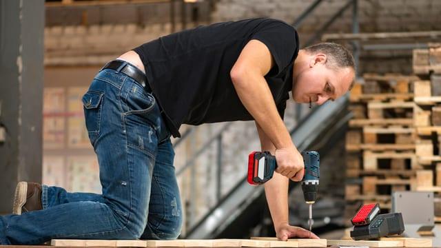Mann kniet auf einer Holzplatte und bearbeitet sie mit einem Akkuschrauber.