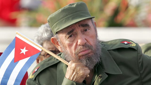 Castro in grüner Uniform. In der Hand die kubanische Flagge, das Kinn auf der rechten Hand aufgestützt.