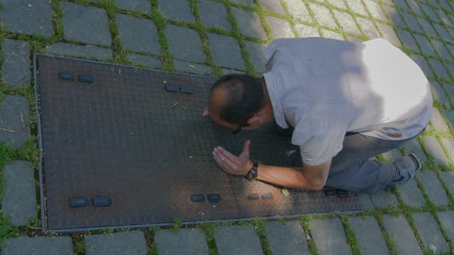 SRF Digital-Mann Reto Widmer kniend auf dem rostigen Schacht, der das Bodensee-Glasfaserkabel abdeckt.
