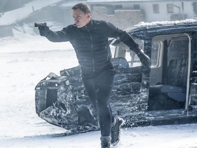 James Bond mit einer Pistole in der Hand vor einem Helikopter-Wrack.