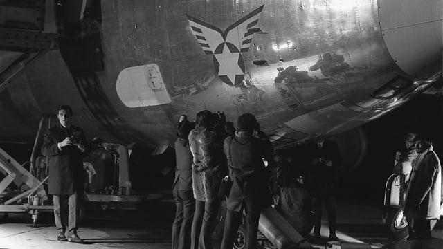 Fotografen stehen vor dem Flugzeug und nehmen die Einschusslöcher auf.