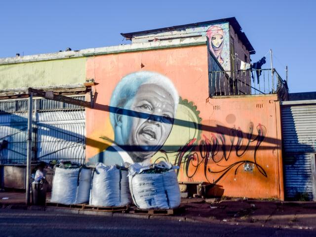 Grafitto, das einen älteren Nelson Mandela zeigt, auf der Rückseite eines Hauses.