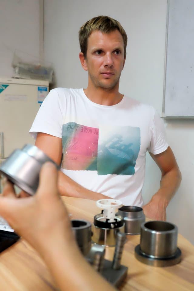 Alex Hofer mit skeptischem Blick an einem Tisch vor Werkteilen.