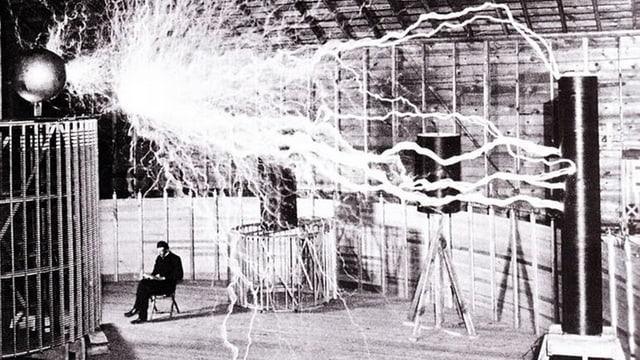 Nikolas Tesla sitzt auf einem Stuhl im Labor, über ihm entladen sich Blitze.