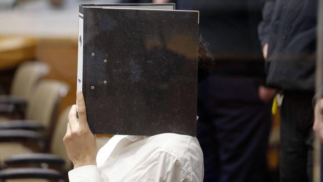 Ein Angeklagter hält sich einen Aktenordner vor das Gesicht.