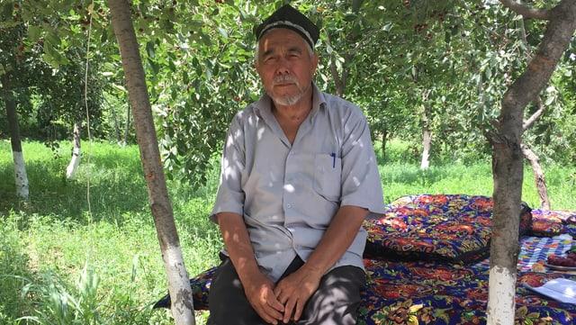 Ein Mann mit schwarzer Mütze sitzt unter einem Baum.