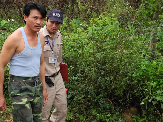 Ein Mann in Unterhemd und einer in beiger Uniform neben einem Gebüsch, in dem eine Hutgrosse Bombe liegt.