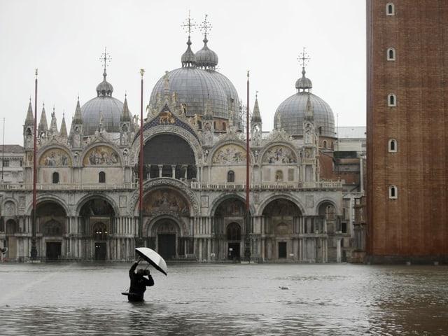 Sin la plazza da Marcus a Venezia emprova in fotograf da fotografar la renumada baselgia. El stat fin tar la taglia en l'aua.