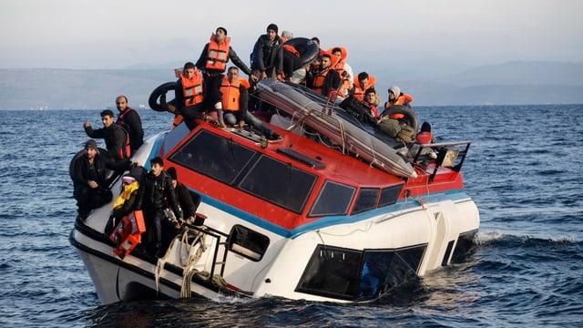 Flüchtlinge sitzen auf einem Boot, das fast am Untergehen ist