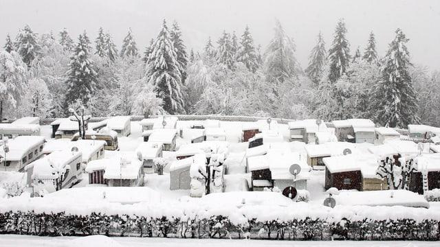 Campingwagen und Häuschen im Schnee.
