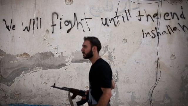 Ein Mann mit einem Gewehr läuft vor einer Mauer, auf der steht: «Wir werden bis zum Enden kämpfen.»