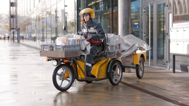 Ein Zustellbote auf einem Dreirad-Elektro-Roller.