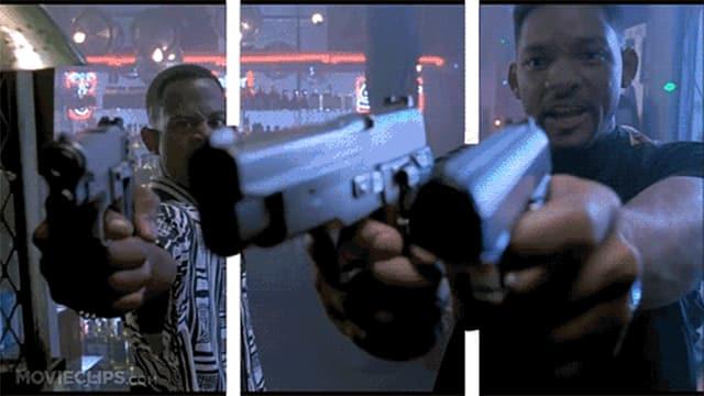 Zwei Schauspieler ziehen ihre Handfeuerwaffen und zielen auf den Betrachter.