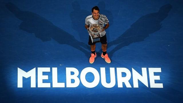 Federer posiert mit der Trophäe auf dem Centre Court vor der Aufschrift «Melbourne».