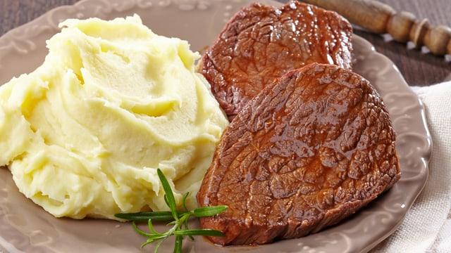 Teller mit Kartoffelstock und Fleischstücken.