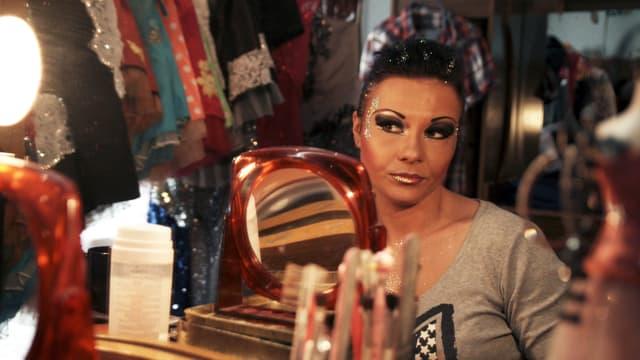 Eine Frau sitzt vor dem Spiegel und schminkt sich.