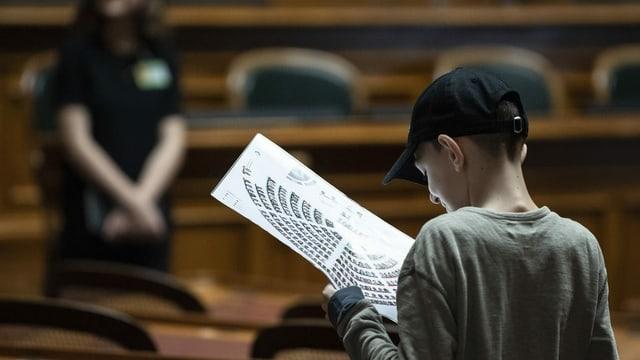 Ein Junge studiert im Bundeshaus den Sitzplan des Nationalrats.