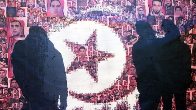Menschliche Silhouetten vor eine Poster, das die Flagge Tunesiens zeigt. Sie besteht aus zahlreichen Fotoporträts von jungen Männern.