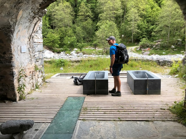 Mann steht vor Badewannen aus Stein