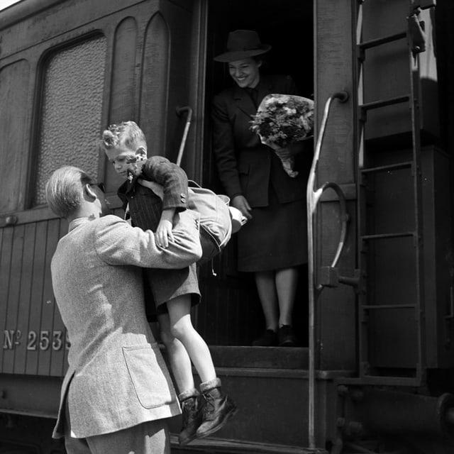 eine schwarz-weiss Fotografie, wie ein Kind von einem Mann aus dem Zug gehoben wird