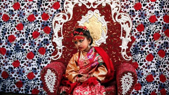 Ein Mädchen in gläzenden Kleidern sitzt auf einem Trohn vor einer mit Blumen bemalten Wand.