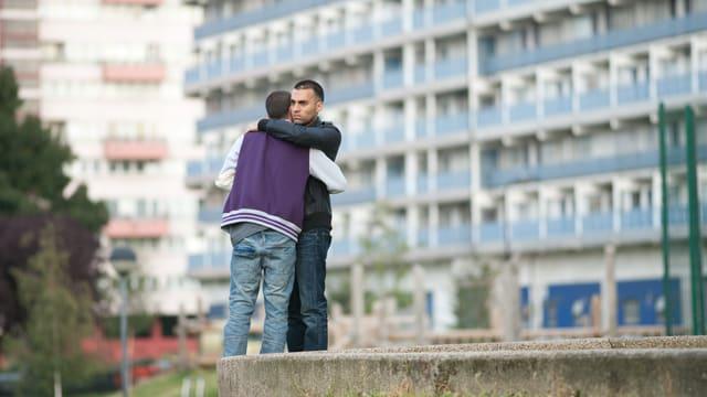 Zwei Brüder umarmen sich.