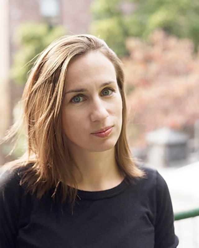 Eine Frau mit langem schwarzen Haar und blauen Augen.