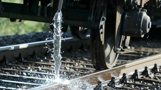 Ein Zug begiesst Schienen mit Wasser.