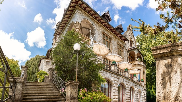 Eine bewachsene Villa mit Terrasse bei schönem Wetter.