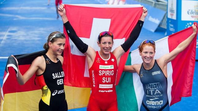 Nicola Spirig hält jubelnd die Schweizer Fahne in die Höhe, an ihrer Seite stehen die Silber- und Bronze-Medaillengewinnerinnen.