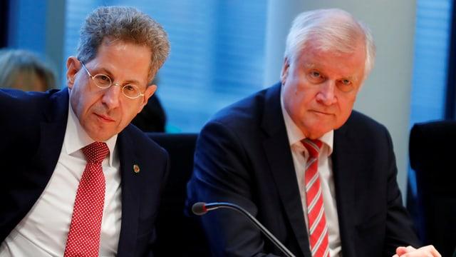 Hans-Georg Maassen und Horst Seehofer sitzen an einem Tisch vor Mikrofon.