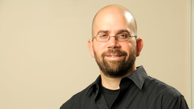 Porträt von Anthony Graesch mit Brille, Glatze und schwarzem Hemd.