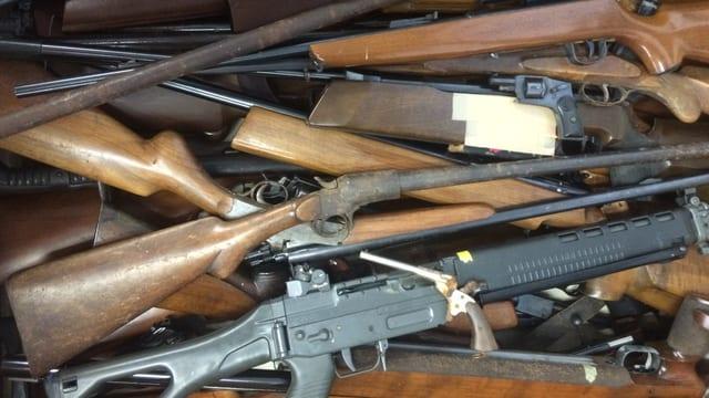 Verschiedenen Gewehre und Pistolen, die kreuz und quer auf einem Haufen liegen