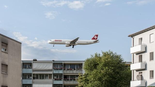 Ein Flugzeug überquert eine Wohnsiedlung.