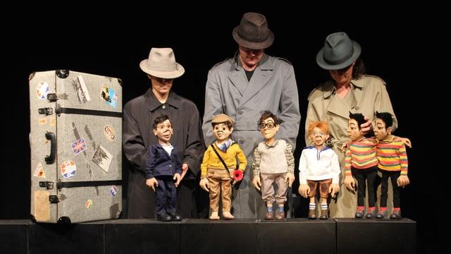 Drei Puppenspieler und fünf Figuren auf der Bühne.