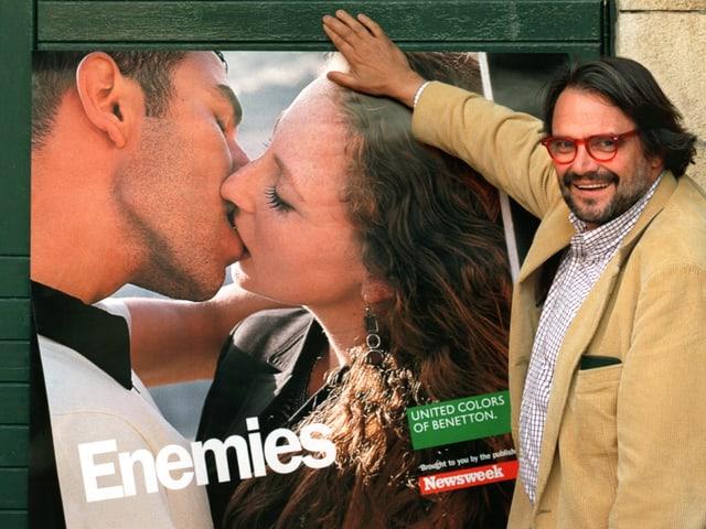 Toscani vor einem Plakat, auf dem ein jüdisches Mädchen einen Palestinenser küsst. Im unteren Teil ist das Logo der Firma Benetton zu erkennen.