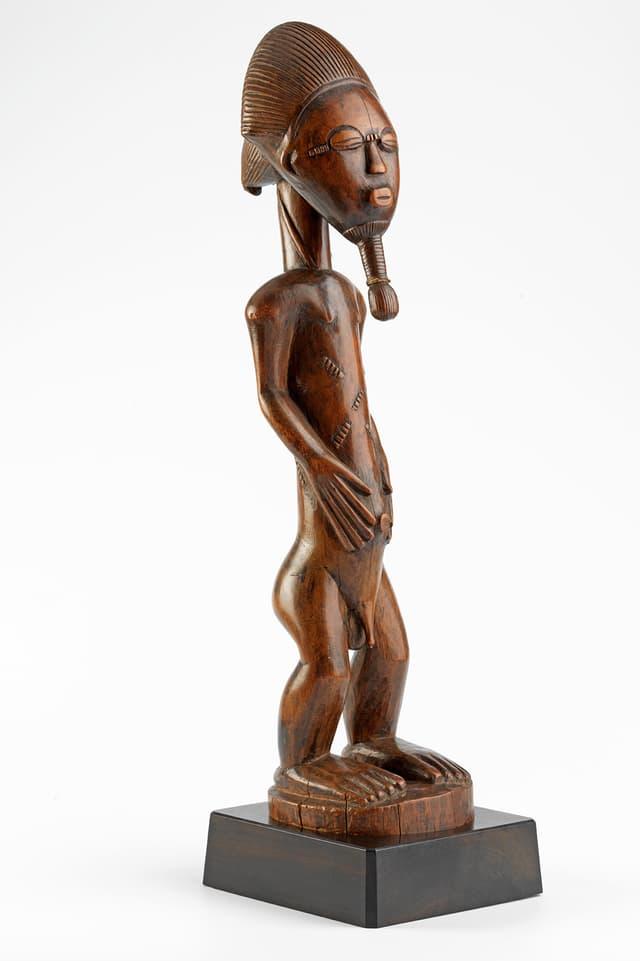 Eine männliche Figur aus Holz, die auf einem Sockel steht.