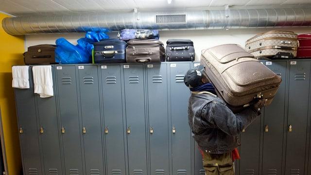 Ein Flüchtling in einer Asylunterkunft hievt einen Koffer von einem Spind herunter.